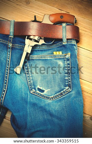 silver revolver under a leather belt of blue jeans. instagram image filter retro style - stock photo