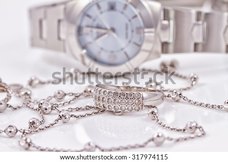 Silver ring and chain on the background of women's watches - stock photo
