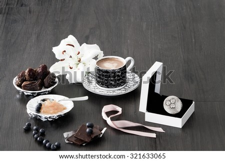 Silver ring gift setting with morning coffee, dry dates, orange marmalade, blueberries and white lily flower - stock photo