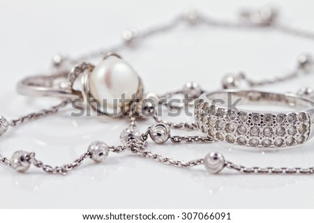 Silver ring with precious stones and pearl are together with a silver chain on acrylic - stock photo