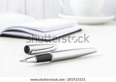 silver roller pen with notebook and coffee cup on white background