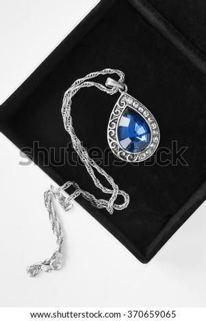 Silver sapphire pendant in velvet box closeup - stock photo