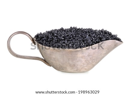 Silver sauceboat with black caviar on white background - stock photo