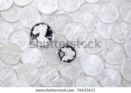 Silver shiny one dollar coins isolated on blurred money background - stock photo