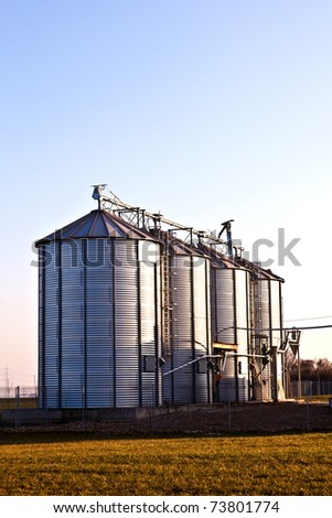 silver silos in the field - stock photo