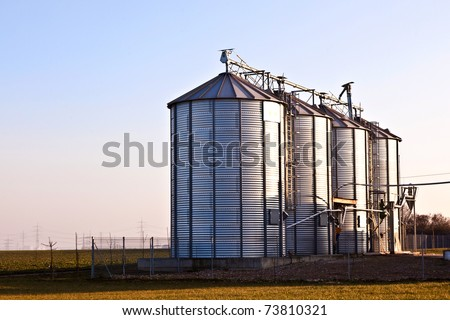 silver silos in the field - stock photo