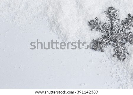 Silver snowflake on snowy background, close up