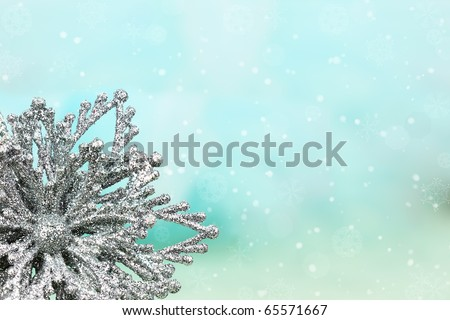 Silver snowflake ornament against a blue background with copyspace. Shallow DOF. - stock photo
