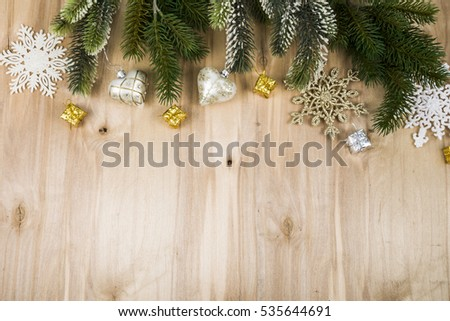 Silver snowflakes and fir branches on a wooden table. Christmas decorations closeup.