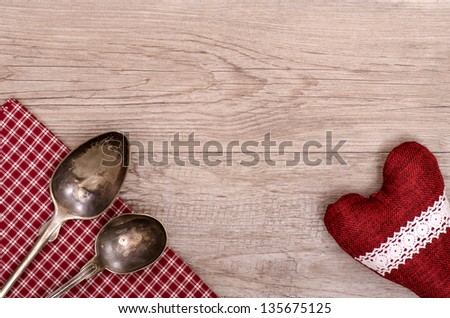 Silver spoon and table cloth with heart on a wooden board - stock photo