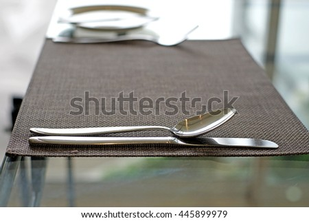 silver spoon fork  and knife on tablecloth