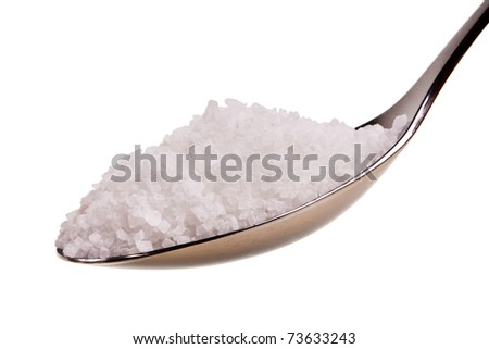 Silver spoon full of white crystal sugar isolated over white background.