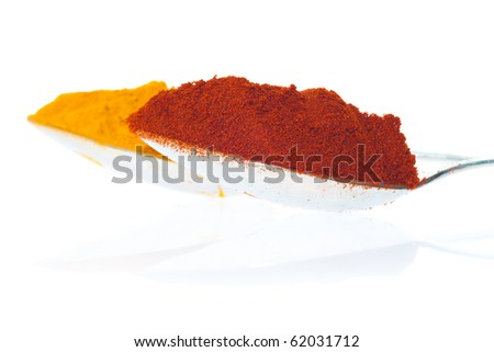 Silver spoons containing curry and paprika powder on a white background