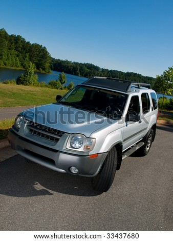 Silver Sports Utility Vehicle high angle lake view SUV - stock photo
