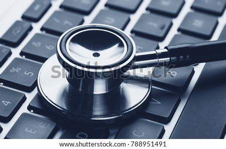 Silver stethoscope lying down on an laptop, blue toned