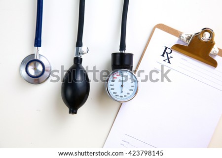 Silver stethoscope lying down on an laptop, toned blue - stock photo