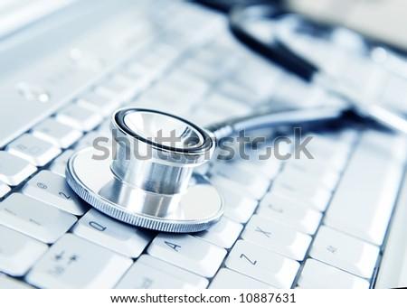 Silver stethoscope on modern silver keyboard - stock photo