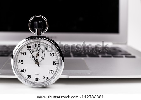 Silver stopwatch with silver laptop in the background - stock photo