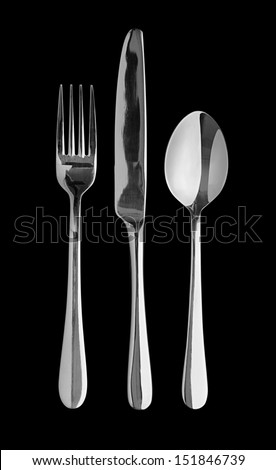 Silver table cutlery or flatware comprising of spoon, knife and fork isolated on a black background. Popular symbol for diners, cafes and good food competitions and food festivals - stock photo