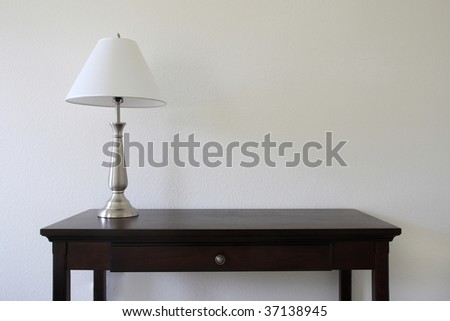 silver table lamp sitting on a wooden table with a white wall in the background and copy space