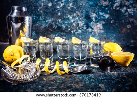 Silver tequila shots with lemon slices and cocktail elements. Alcoholic drinks in shot glasses served in pub or bar - stock photo