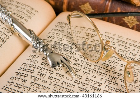 Silver Torah pointer lying on a jewish prayer book - stock photo