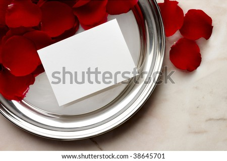 Silver tray, red rose petals, blank white card shot on marble - stock photo