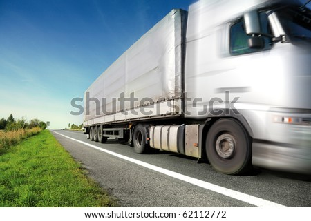 Silver truck driving on country road/motion blur - stock photo