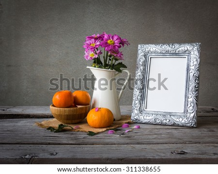 Silver vintage photo frame and flowers on wooden table over grunge background - stock photo