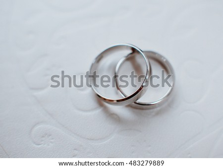 Silver wedding rings lie on the white tablecloth
