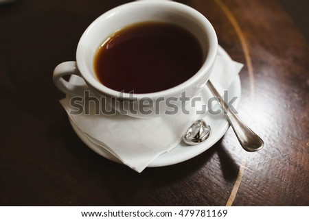 Silver wedding rings lying near cup of coffee