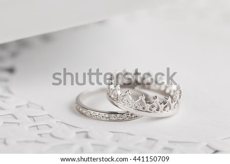 Silver wedding rings with crown shape on gray background. Shallow focus