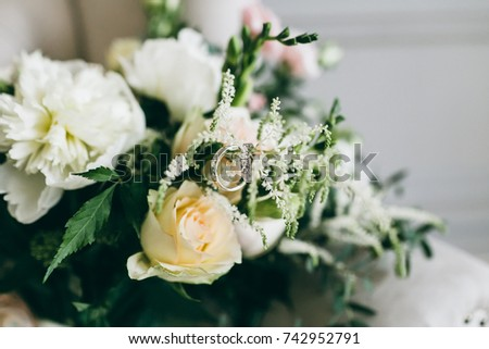 Silver wedding rings with gems on the bunch of wedding bouquet. Artwork