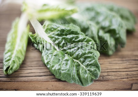 Silverbeet leaves on wooden background with selective focus - stock photo