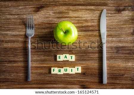 Silverware and apple on wooden vintage table with sign Eat fruit - stock photo