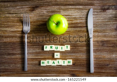 Silverware and apple set on wooden table with sign saying Fruit equals health - stock photo