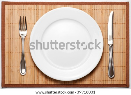 Silverware (metal fork, knife and ceramic white plate) on bamboo mat - stock photo