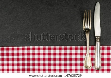 Silverware on a slate plate with a red checkered tablecloth - stock photo