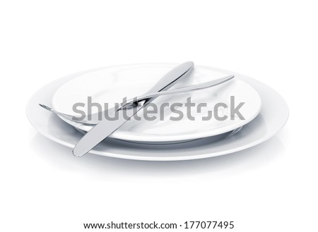 Silverware or flatware set of fork and knife over plates. Isolated on white background - stock photo