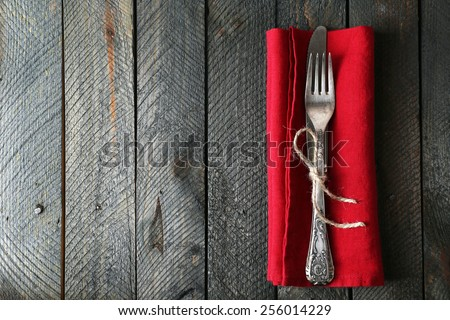 Silverware tied with rope on red napkin on wooden planks background - stock photo