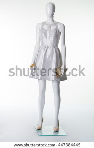 Silvery dress on mannequin with golden accessories. Evening dress for celebration.
