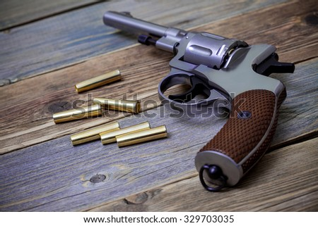 silvery Nagan revolver with cartridges on aged wood background, close-up, part of - stock photo