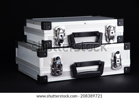Silvery suitcases on black background - stock photo