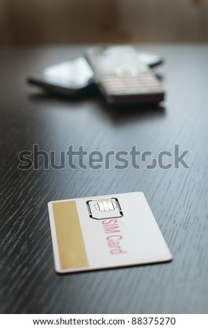 SIM card and mobile phone on table - stock photo