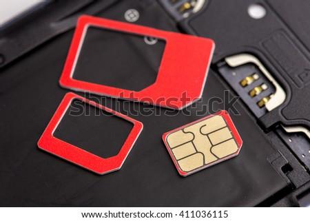Sim card and sim card adapter put on smart phone - stock photo