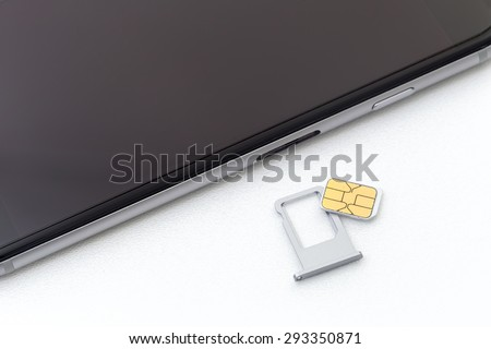 Sim card and sim card tray put nearly cell phone on white background - stock photo