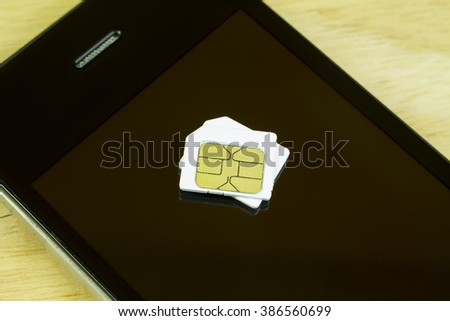 sim card and smart phone on wood background - stock photo