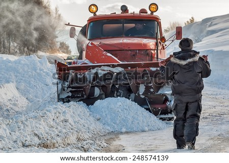 Sim, Russia - February 25, 2008: Snowplow removes snow from intercity road from snow blizzard. Worker controls snow cleaning process - stock photo