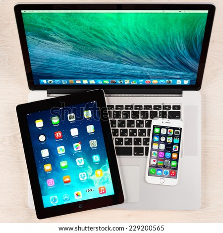 SIMFEROPOL, RUSSIA - NOVEMBER 04, 2014: Apple iPhone 6, iPad and Macbook pro over table. Apple Inc. is an American multinational corporation that designs, develops, and sells consumer electronics. - stock photo