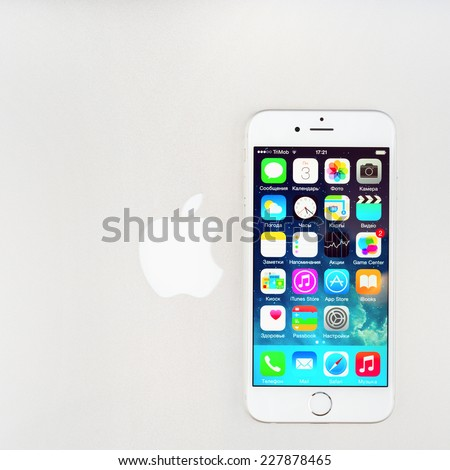 SIMFEROPOL, RUSSIA - NOVEMBER 03, 2014: Apple iPhone 6 over Macbook cover displaying iOS 8.1 homescreen. iOS 8 is the eighth major release of the iOS mobile operating system designed by Apple Inc. - stock photo